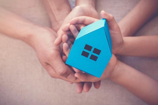 Erwachsene und kinderhände, die weißes haus, familienheim und obdachlosenheimkonzept halten