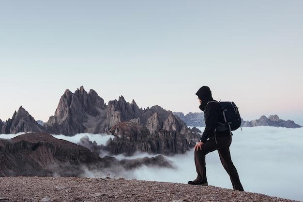 Erwachsene wanderer waling am rande des hügels und beobachten und tolle berge