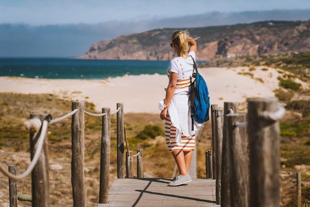 Erwachsene weibliche touristin, die küstenansicht des praia do guincho beach genießt. cascais, portugal