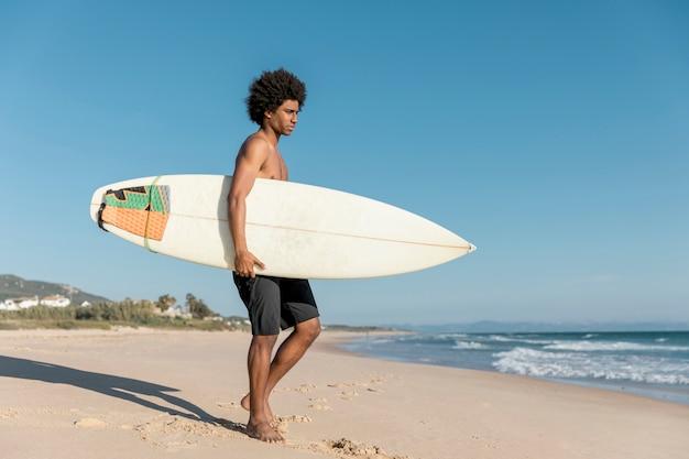 Erwachsener afroamerikanermann, der für das surfen sich vorbereitet