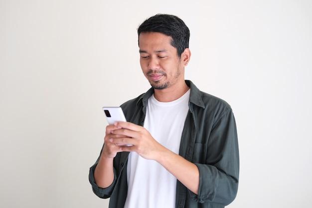 Erwachsener asiatischer junger mann, der zu seinem handy schaut