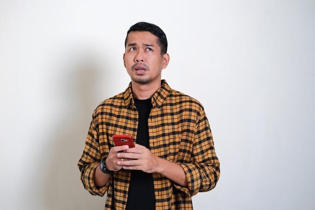 Erwachsener asiatischer mann denkt etwas, während er auf seinem handy tippt