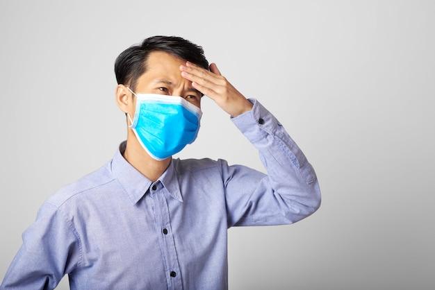Erwachsener asiatischer mann, der chirurgische maske trägt, die mund- und nasenwitz bedeckt