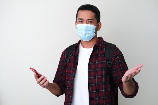 Erwachsener asiatischer mann, der eine medizinische schutzmaske trägt und ein mobiltelefon hält, das unentschlossene geste zeigt