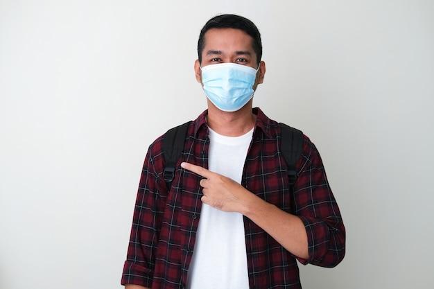 Erwachsener asiatischer mann, der eine medizinische schutzmaske trägt und mit dem finger auf seine seite zeigt