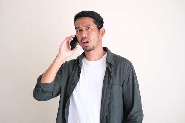 Erwachsener asiatischer mann, der einen verwirrenden gesichtsausdruck zeigt, während er einen anruf mit dem mobiltelefon beantwortet