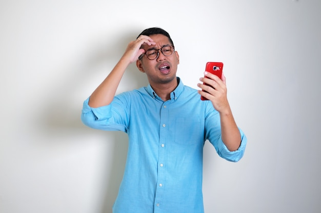 Erwachsener asiatischer mann, der enttäuschten ausdruck zeigt, während er auf sein handy schaut