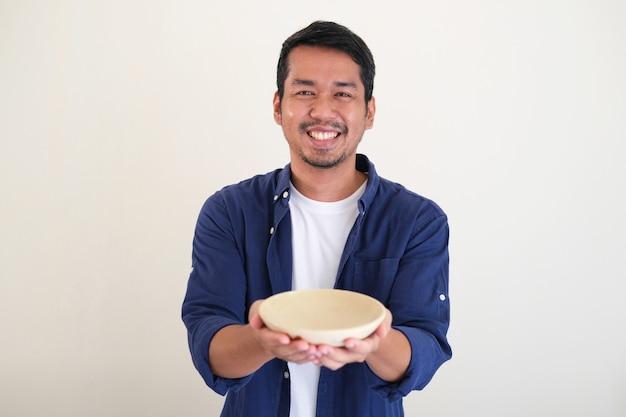 Erwachsener asiatischer mann, der glücklich lächelt, während er leere essschüssel zeigt