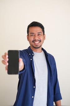 Erwachsener asiatischer mann, der glücklich lächelt, während er leeren handybildschirm zeigt