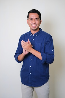 Erwachsener asiatischer mann, der glücklich lächelt, wenn er anderen applaus gibt