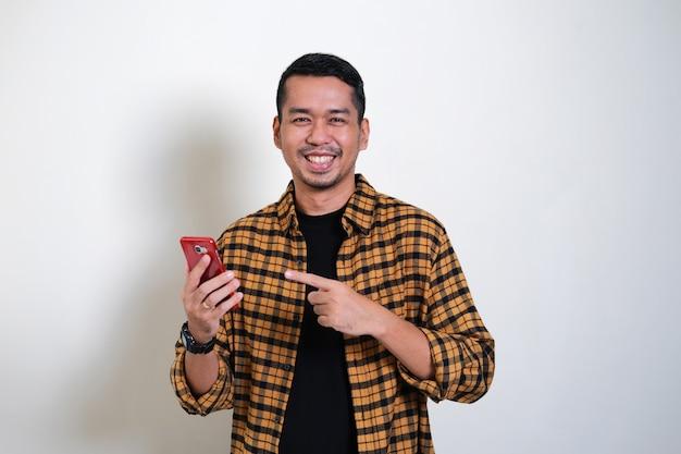 Erwachsener asiatischer mann, der glücklichen ausdruck zeigt, während er auf sein handy zeigt
