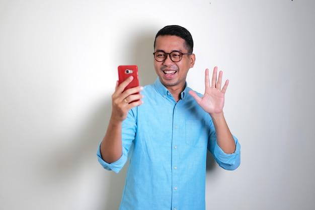Erwachsener asiatischer mann, der glücklichen ausdruck zeigt, wenn er während des videoanrufs mit der hand winkt