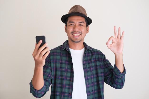 Erwachsener asiatischer mann, der lächelt und ok-fingerzeichen gibt, während er handy hält