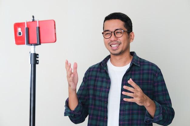 Erwachsener asiatischer mann, der lächelt, während er etwas über eine mobiltelefonkonferenz präsentiert