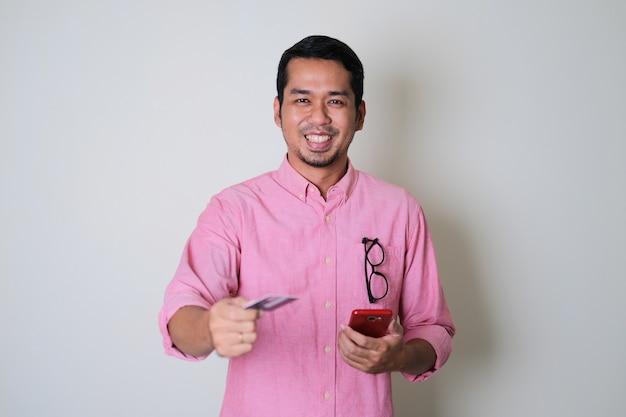 Erwachsener asiatischer mann, der lächelt, während er seine kreditkarte zum bezahlen von sachen gibt