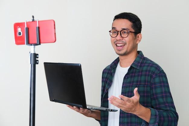 Erwachsener asiatischer mann, der laptop-computer hält, während er mit handy-videoanruf-konferenz präsentiert