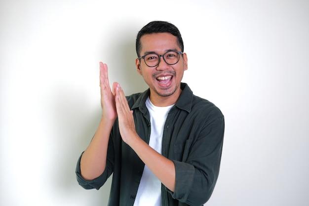 Erwachsener asiatischer mann, der mit glücklichem ausdruck klatscht, um anerkennung zu geben