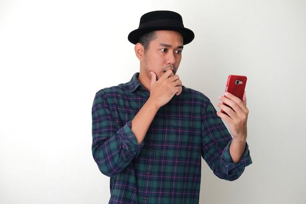 Erwachsener asiatischer mann, der schockierten gesichtsausdruck zeigt, während er auf sein handy schaut