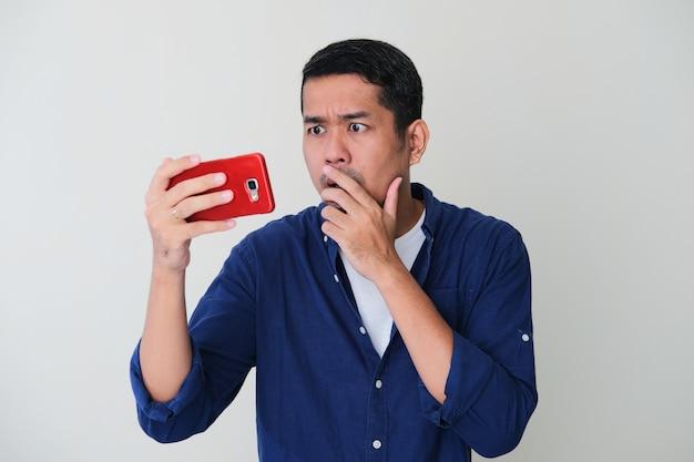 Erwachsener asiatischer mann, der schockierten gesichtsausdruck zeigt, wenn er auf sein handy schaut