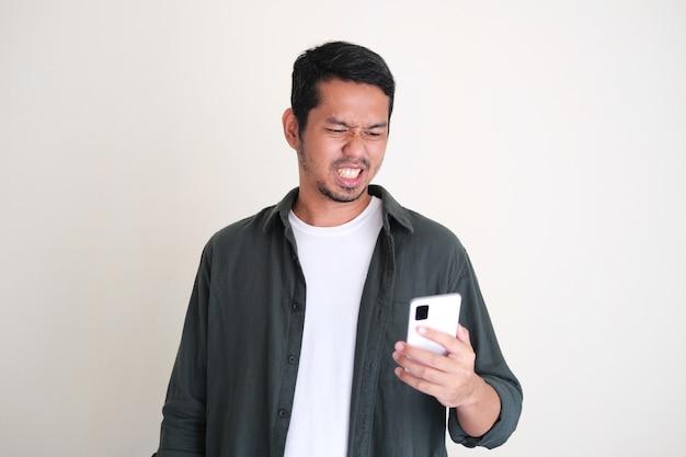 Erwachsener asiatischer mann, der sein handy mit angewidertem gesichtsausdruck hält und anschaut