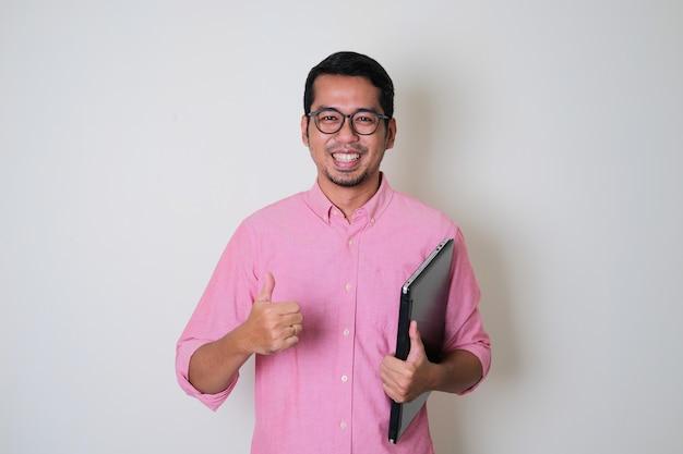 Erwachsener asiatischer mann, der selbstbewusst lächelt, während er einen laptop hält und den daumen aufgibt