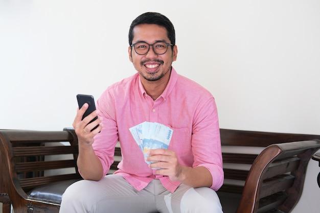 Erwachsener asiatischer mann, der selbstbewusst lächelt, während er handy hält und papiergeld zeigt