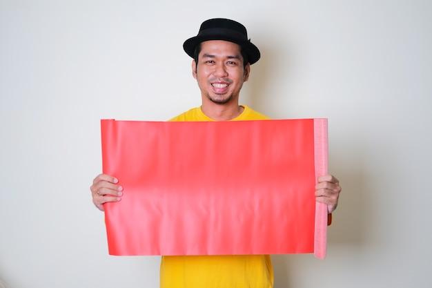 Erwachsener asiatischer mann, der selbstbewusst lächelt, während er leeres rotes farbpapier hält