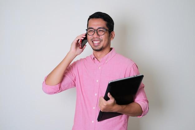 Erwachsener asiatischer mann, der selbstbewusst lächelt, wenn er einen anruf mit dem handy beantwortet
