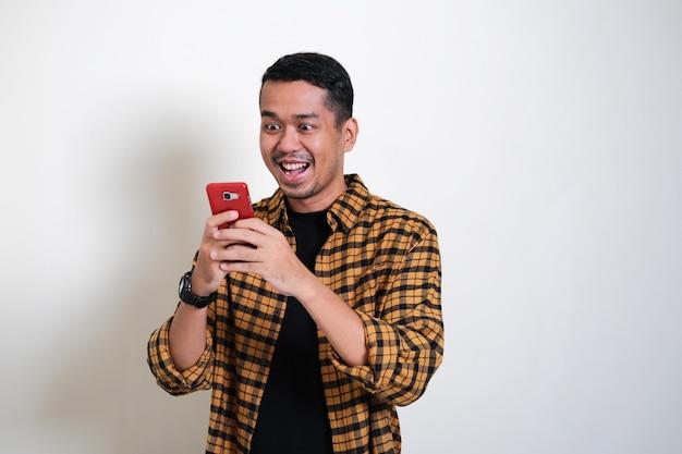 Erwachsener asiatischer mann, der überraschten gesichtsausdruck zeigt, während er nachricht in seinem handy liest