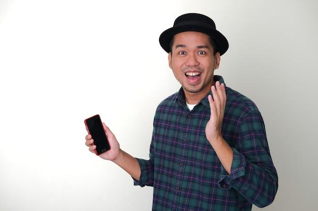 Erwachsener asiatischer mann, der überraschten gesichtsausdruck zeigt, während er sein handy hält