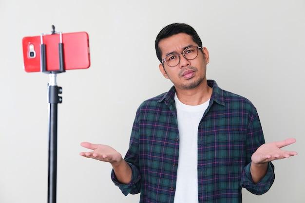 Erwachsener asiatischer mann, der verwirrte geste vor seinem handy zeigt