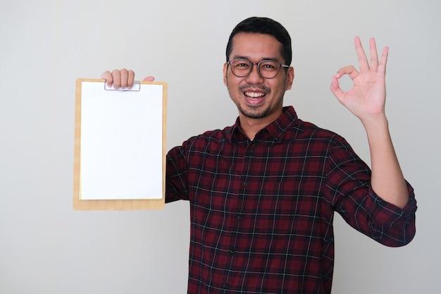 Erwachsener asiatischer mann, der weißes leeres papier hält und ok-fingerzeichen gibt