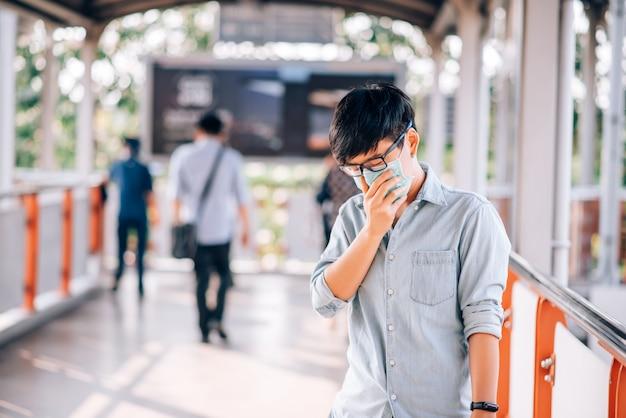 Erwachsener asiatischer mann mit medizinischer maske, die auf der straße geht