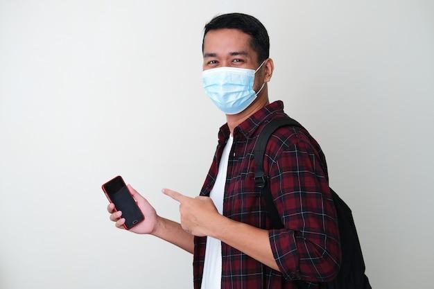 Erwachsener asiatischer mann mit medizinischer schutzmaske, der ein handtelefon hält und mit dem finger darauf zeigt