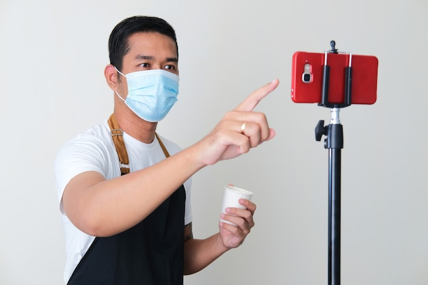 Erwachsener asiatischer mann mit schürze und medizinischer maske, der online-bestellungen mit dem mobiltelefon entgegennimmt