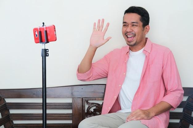 Erwachsener asiatischer mann winkt mit glücklichem gesichtsausdruck während des videoanrufs