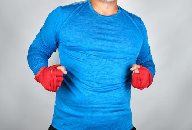 Erwachsener athlet in der blauen kleidung, hände eingewickelt in einem roten elastischen verband