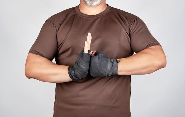 Erwachsener athlet in der braunen kleidung mit verbundenen händen schwärzen textilsportverband
