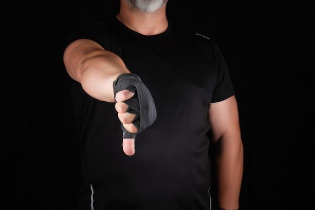 Erwachsener athlet in der schwarzen uniform und in den händen, die mit textilverband zurückgewickelt werden, zeigt gestenabneigung