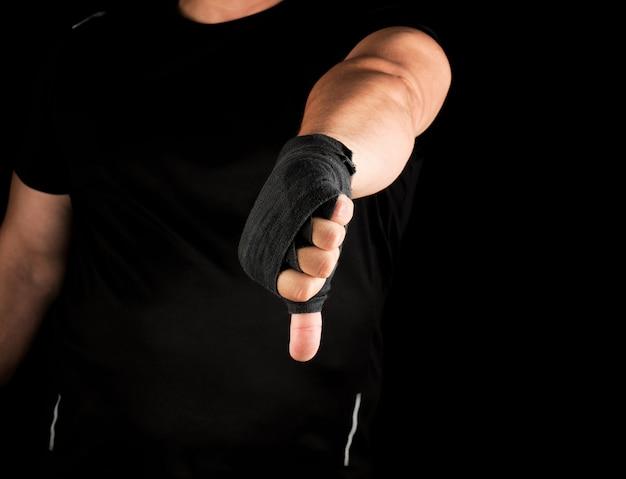 Erwachsener athlet in der schwarzen uniform und in den händen zurückgewickelt mit textilverband