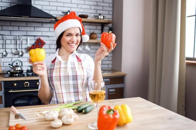 Erwachsener attraktiver frauenstand in der küche und in der aufstellung. paprika in händen halten. tragen sie einen roten festlichen hut. weihnachten oder neujahr feiern. allein kochen.