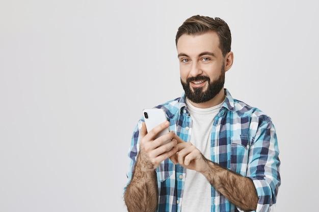 Erwachsener bärtiger mann, der online-bestellung mit handy macht
