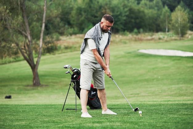 Erwachsener bärtiger mann, der sich darauf konzentriert, den golf in dem herrlichen grünen rasen zu spielen.