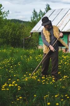 Erwachsener bärtiger mann mit einer sense mäht gras in seinem haus auf einer wiese in einem sommerdorf