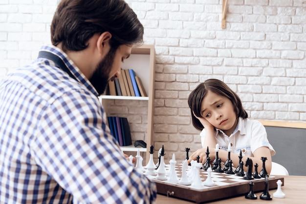 Erwachsener bärtiger vater spielt schach mit jugendlich sohn zu hause.