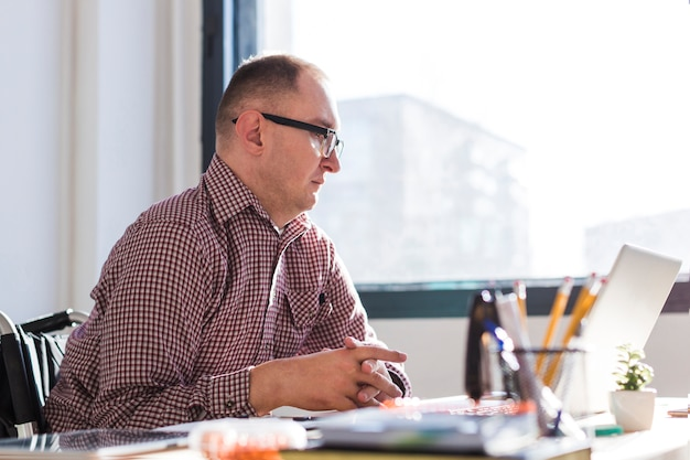 Erwachsener behinderter mann, der im büro arbeitet