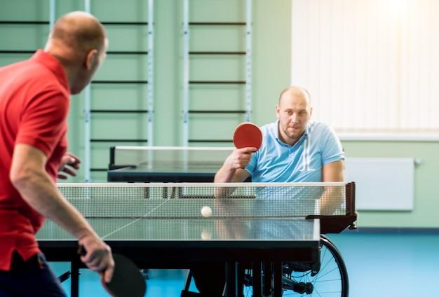 Erwachsener behinderter mann im rollstuhl spielt mit seinem trainer tischtennis