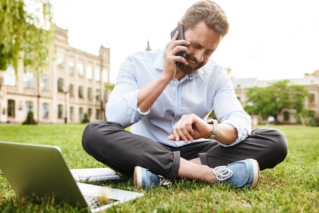 Erwachsener europäischer mann in geschäftskleidung, der smartwatch beim sitzen auf gras im park mit gekreuzten beinen betrachtet und geschäftsanruf hat