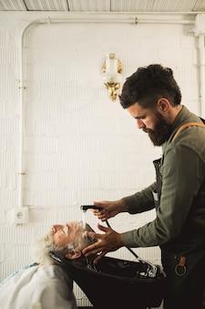 Erwachsener friseur, der haar des alten mannes auf rückspülung wäscht