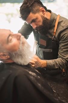Erwachsener friseur, der kundenbart am friseursalon rasiert